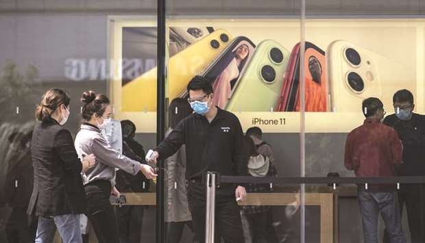 An employee wearing a protective mask checks the temperature of customers outside an Apple Inc store