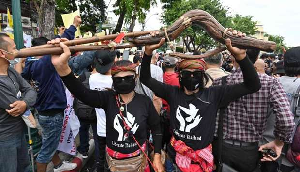 Anti-government protesters carry a wooden yoke, used to tie buffalo or oxen during ploughing season,
