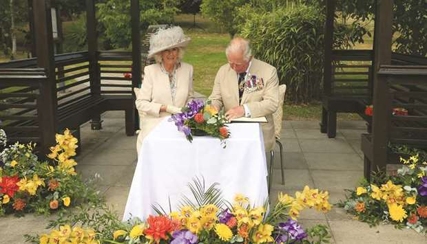 Prince Charles and Camilla, Duchess of Cornwall, sign the visitors' book during the VJ Day National
