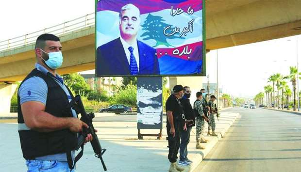Members of security forces stand guard yesterday near a billboard depicting Lebanon's former Prime M