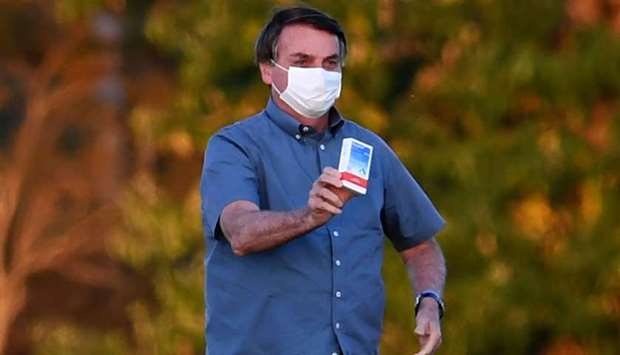 Brazilian President Jair Bolsonaro shows a box of hydroxychloroquine to supporters outside the Alvor
