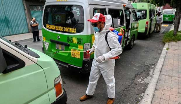 A cleaning worker wearing personal protective equipment (PPE) disinfects a public tranport vans in M