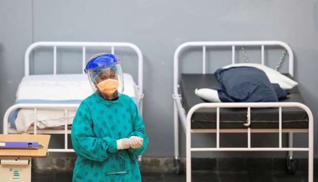 A health worker walks between beds at a temporary field hospital set up by Medecins Sans Frontieres