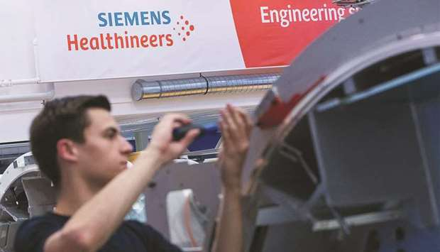 An employee works on the gantry of a Siemens Somatom computerised tomography (CT) scanner machine on