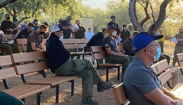 BRIEFING: Firefighters wear face masks at a morning briefing on the Bighorn Fire, north of Tucson, A