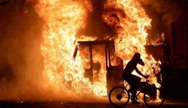 A man on a bike rides past a city truck on fire outside the Kenosha County Courthouse in Kenosha, Wi