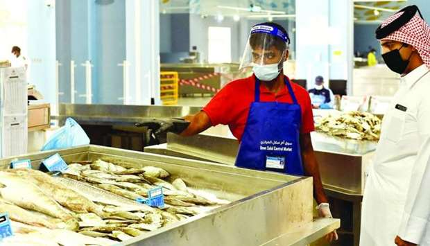 A salesman interacts with a customer at the new fish market at Umm Slal Central Market.