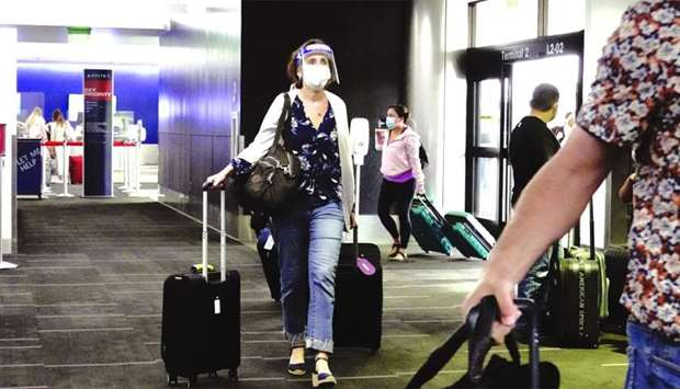 A traveller wearing a protective mask and face shield walks into Terminal 2 at Los Angeles Internati