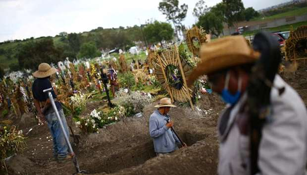 Cemetery workers dig new graves at the Xico cemetery on the outskirts of Mexico City, as the coronav