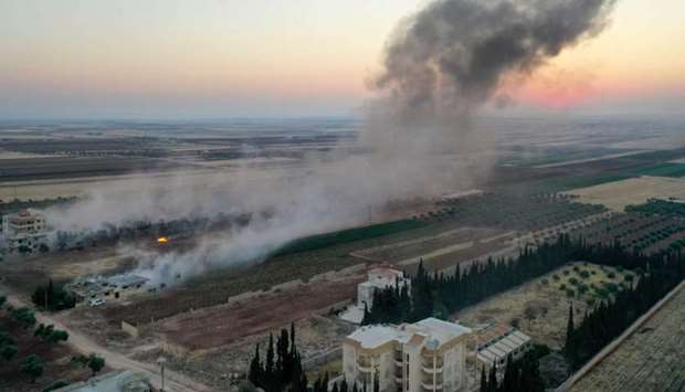 Smoke billows following airstrikes and shelling on the town of Binnish in Syria's jihadist-controlle