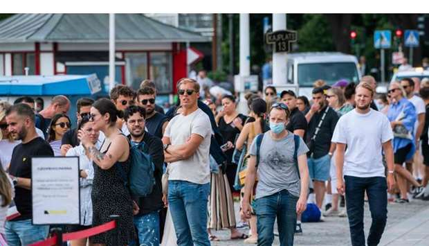 A man wearing a protective face mask walking next to travellers as they queue up to board a boat at