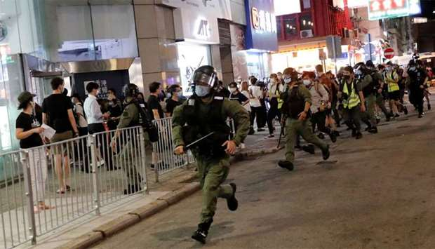 Riot police chase pro-democracy protesters during a protest near Prince Edward station to mark one y