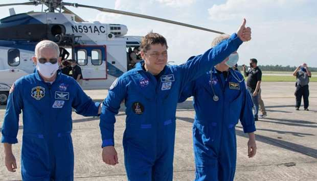 NASA astronaut Robert Behnken giving a thumbs up to onlookers as he boards a plane at Naval Air Stat