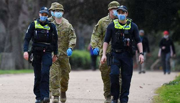 Police officers and soldiers patrol a popular running track in Melbourne