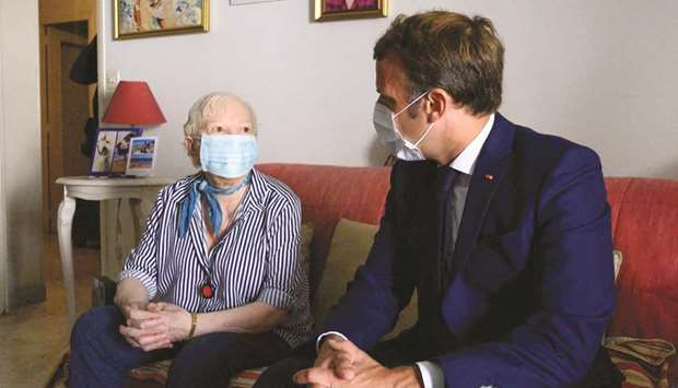 French President Emmanuel Macron (right) pays a visit to Gisele Charles, 80, who lives alone in Toul