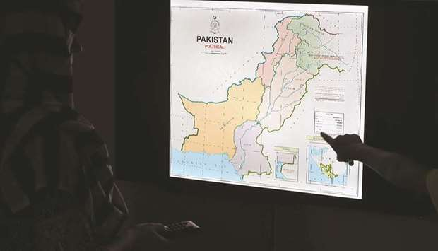 Journalists look at Pakistan's new political map on a screen at the Daily Metro Watch newspaper offi