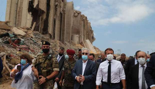 French President Emmanuel Macron and Foreign Minister Jean-Yves Le Drian inspect the damages at the