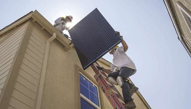 Contractors move a SunRun solar panel up a ladder to the roof of a new home in Sacramento, Californi