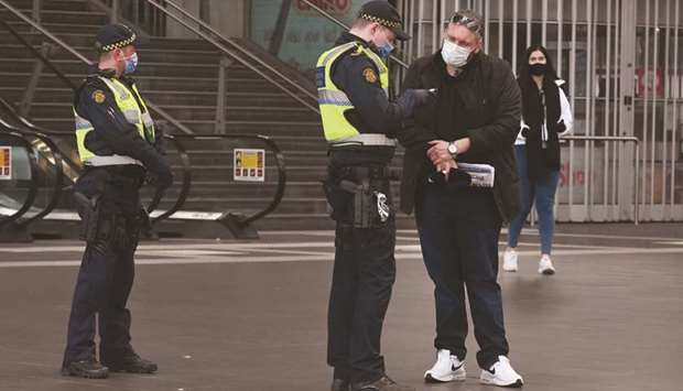 A Protective Services Officer speaks to a man at the Southern Cross Station in Melbourne.