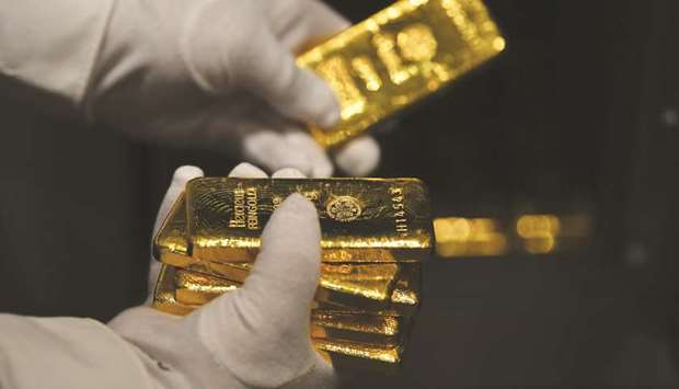 An employee holds gold bars in the precious metals vault at Pro Aurum KG in Munich. Gold's surge to