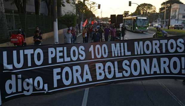 "Health union members hold a banner reading ""Mourning for the 100,000 dead. I say, Bolsonaro out!"" as"