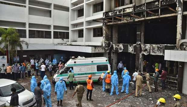 Rescue workers look for survivors after a fire broke out in a hotel that was being used as a coronav