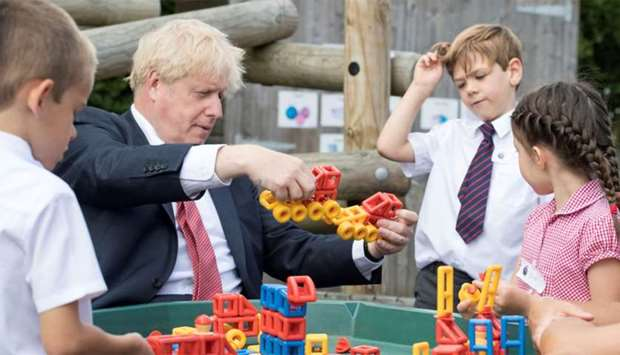 Britain's Prime Minister Boris Johnson plays with toys as students look on during a visit to The Dis
