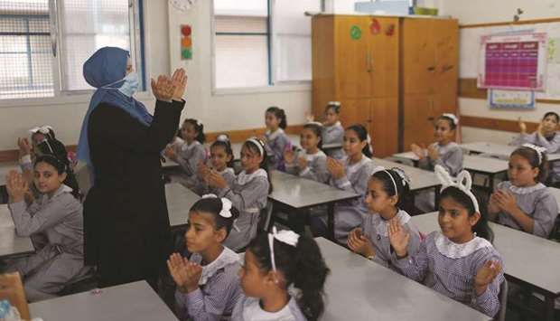 A teacher wearing a protective face mask gestures as Palestinian students sit in a classroom at a Un