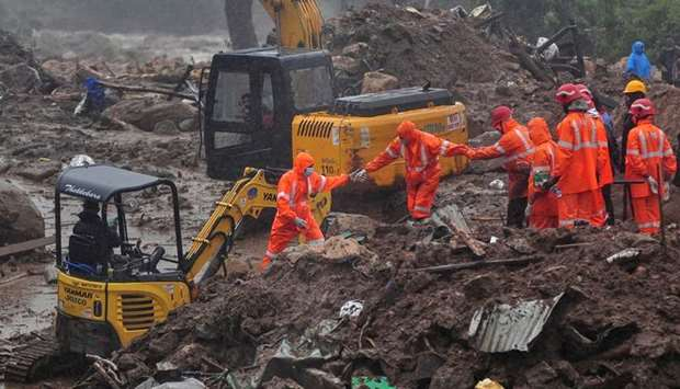 Rescue workers look for survivors at the site of a landslide during heavy rains in Idukki, Kerala, I
