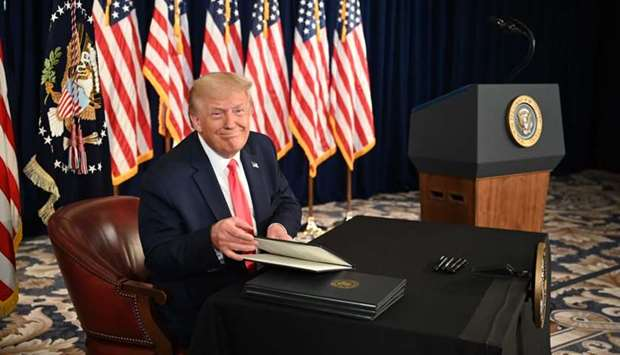 US President Donald Trump signs executive orders extending coronavirus economic relief, during a new