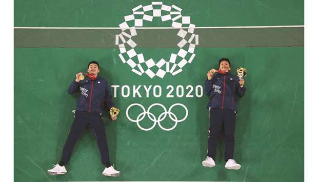 Taiwan's Lee Yang (right) and Taiwan's Wang Chi-lin pose on the court with their men's doubles badmi