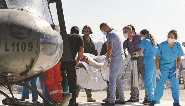 A man with severe burn injuries sustained in the fuel tank explosion is carried on a stretcher from