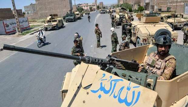 An Afghan National Army commando stands guard on top of a vehicle along the road in Enjil district o