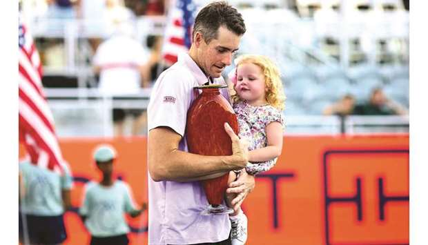 John Isner of the United States holds his daughter, Hunter Grace, in one arm and the winner's trophy