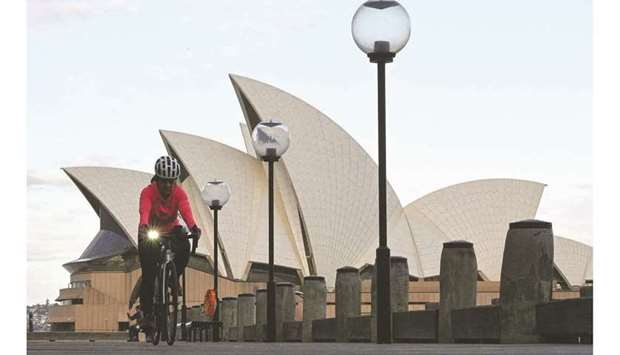 A woman rides on a bicycle in front of the landmark Sydney Opera House during lockdown yesterday.