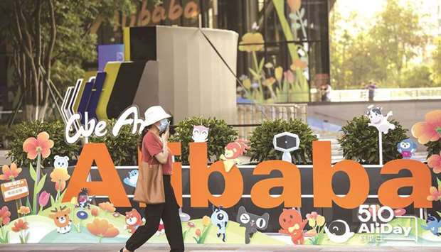 A person walks past a sign at the Alibaba Group Holding headquarters in Hangzhou, China. Alibaba rep