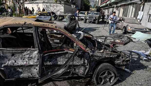 Journalists and security personnel are seen in the backdrop of the wreckage of a car a day after an