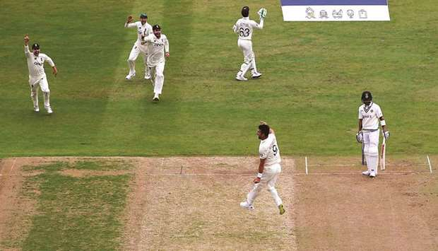England's James Anderson celebrates taking the wicket of India's Virat Kohli with teammates during D