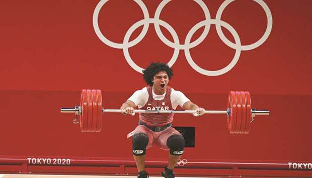 Qatar's Fares Ibrahim celebrates after winning the gold medal in the men's 96kg weightlifting compet