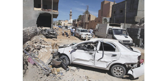 Damaged cars and debris are seen at the site of a bombing that targeted the house of former security