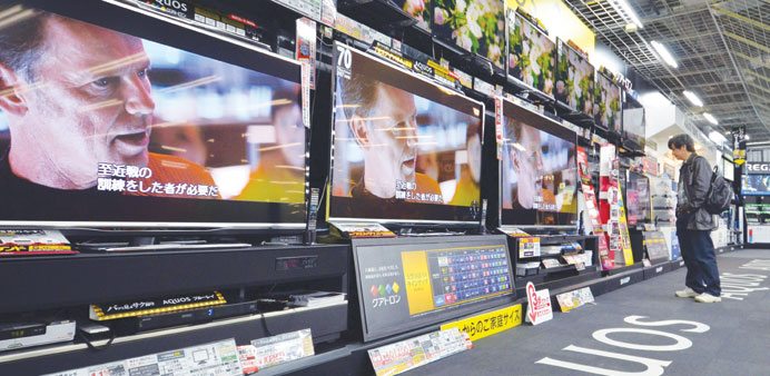 A customer checks LCD television sets manufactured by Sharp at an electronics showroom in Tokyo yest