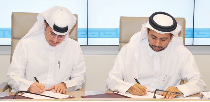 Dr Hassan al-Derham and Yousef al-Naama signing the agreement.