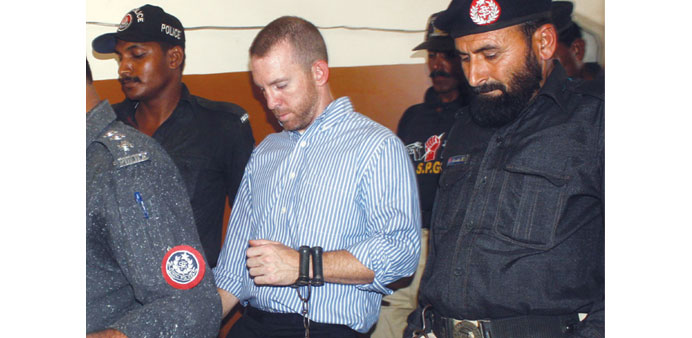 In this photograph taken on May 6, 2014 Pakistani policemen escort an alleged US FBI agent under arr