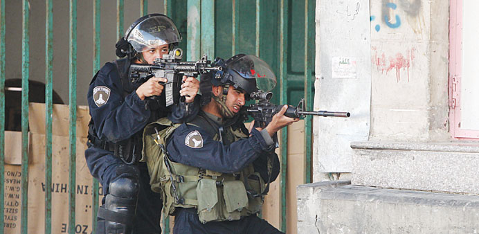 Israeli border guards take aim at Palestinian protesters during clashes following a protest in the W