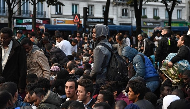 Migrants gather and wait before being evacuated from a makeshift migrant camp