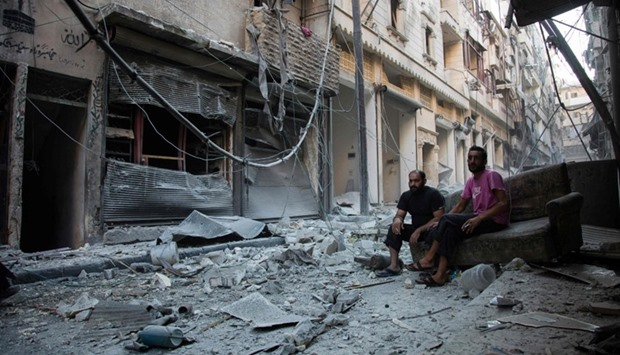 Syrians sit and look at the rubble following an air strike on the rebel-controlled neighbourhood of