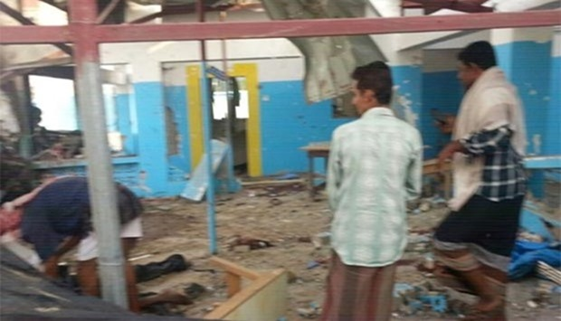 People examining a hospital hit in coalition air strike in Abs, Yemen