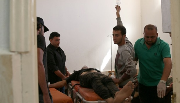 People move an injured man inside a field hospital after an airstrike Dael, Syria.