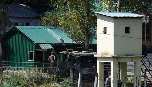 An Indian army soldier looks into a building at an army brigade headquarters during a gunbattle