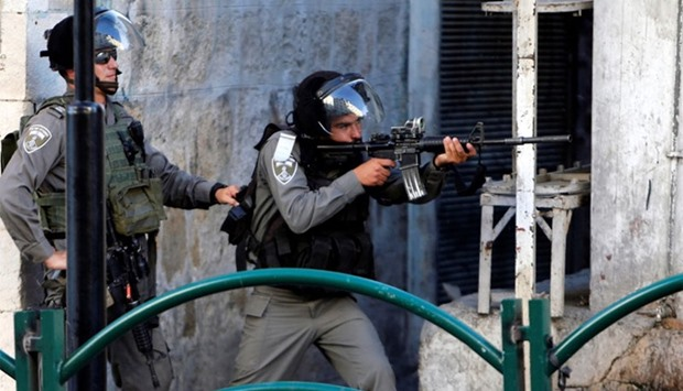 An Israeli border policeman aims his weapon towards Palestinian protesters during clashes in Hebron